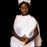 Maimouna poses dressed up as a nurse, in Carnot, Central African Republic. Only the organization Doctors Without Borders brings health care to the displaced families living within the enclave.